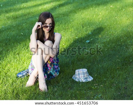 Beautiful slim young girl in  hat and glasses sits  on a green lawn with the phone waiting for friends. - stock photo