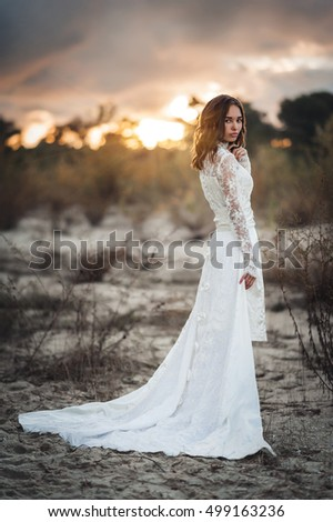 Beautiful, slim, young woman in a white lace dress at sunset.