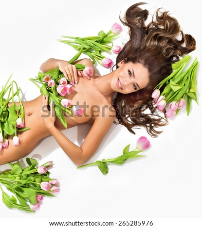 Beautiful slim young woman lying, surrounded by pink tulips. Perfect figure. Spring Flower. Springtime. - stock photo