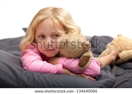beautiful small blond girl  in pink pajamas sleeping with teddy bear