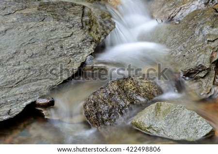 beautiful small serene mountain creek water flow in lush green summer nature over smooth rocks - stock photo