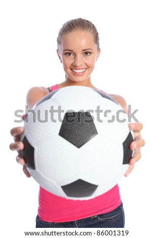 Beautiful smile from soccer player teenage girl holding black and white football outstretched hands. - stock photo