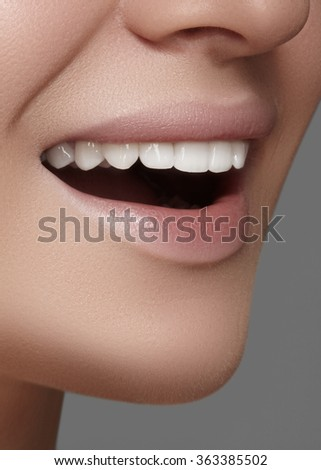 Beautiful smile with white teeth. Dental photo. Macro closeup of perfect female mouth, lipscare rutine. Clean skin. Cosmetics and make-up