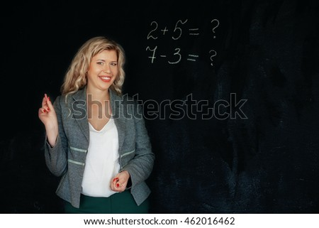Beautiful smiles mathematics teacher at the blackboard. The concept of learning