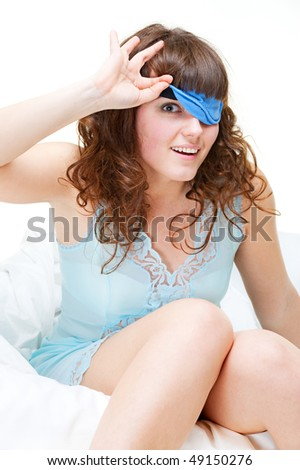 beautiful smiley woman in bandage for eyes sitting on the bed