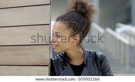 Beautiful smiling african woman in urban background. Young african american woman posing outdoors. Trendy and urban style/ casual clothes.