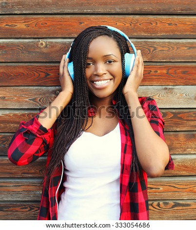 Beautiful smiling african woman with headphones listens to music and having fun in city over wooden background - stock photo