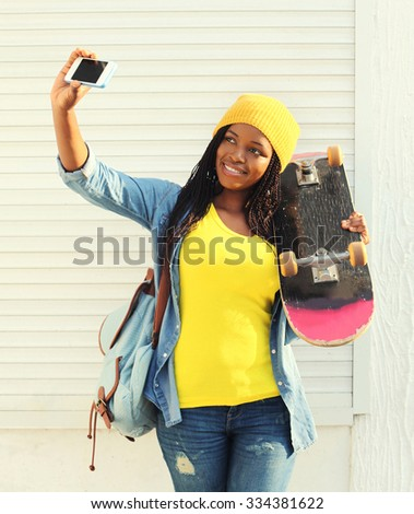 Beautiful smiling african woman with skateboard taking self-portrait picture on smartphone in city, wearing a colorful yellow clothes - stock photo