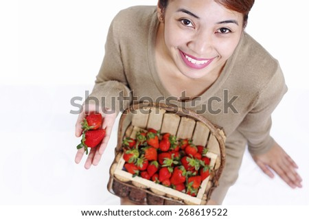 Beautiful smiling asian lady sitting on the floor showing some strawberry in her hand. High angle shot. - stock photo