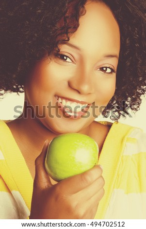 Beautiful smiling black woman holding green apple