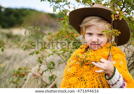 beautiful smiling blond girl with brown hat on her head in autumn field with rose-hip plant