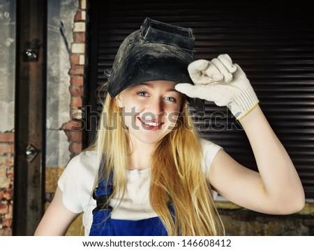 beautiful smiling blond woman in welder helmet - stock photo