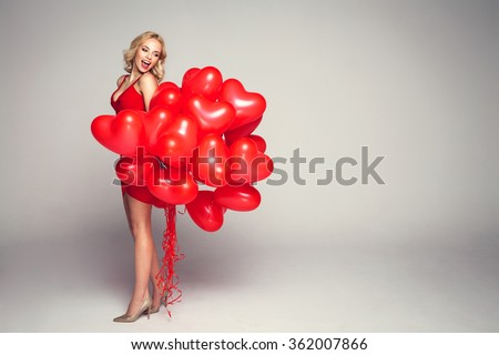 Beautiful smiling blond woman posing on grey background and holding balloons heart. Valentine's day. - stock photo