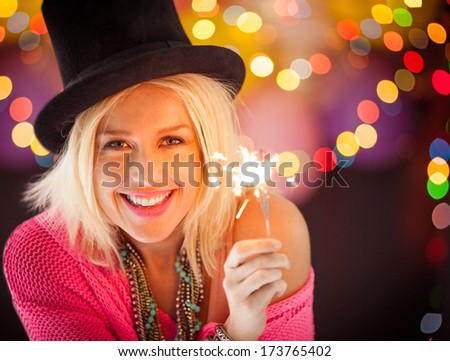 Beautiful smiling blonde holding a sparkler on a New Year's Eve. - stock photo