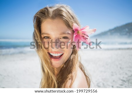 Beautiful smiling blonde with flower hair accessory on the beach on a sunny day - stock photo