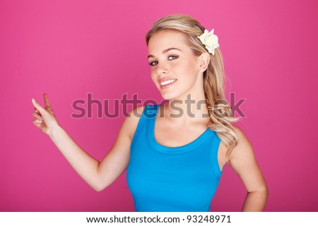 Beautiful smiling blonde woman in blue top pointing with her finger at blank copyspace for your text. - stock photo