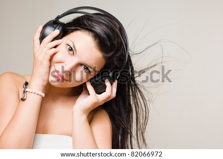 Beautiful smiling brunette in white dress, with flowing hair, enjoying music in headphones. - stock photo