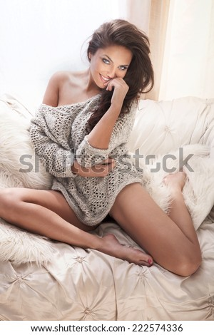 Beautiful smiling brunette woman with long slim legs posing in bedroom, relaxing - stock photo