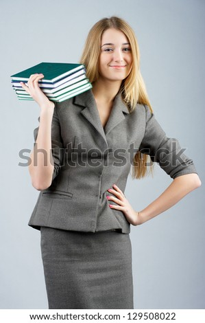 Beautiful smiling business woman with with pile of books in her hand. - stock photo