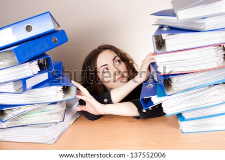 Beautiful smiling businesswoman with a lot of folders at office - stock photo