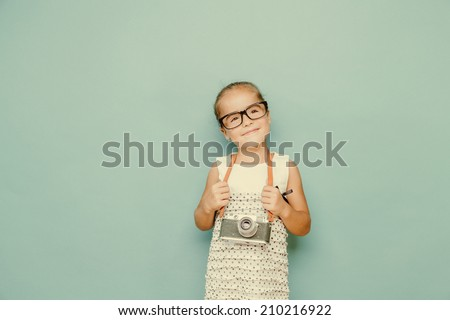 Beautiful smiling child (kid, girl) holding a instant camera - stock photo