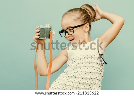 Beautiful smiling child (kid, girl) holding a instant camera