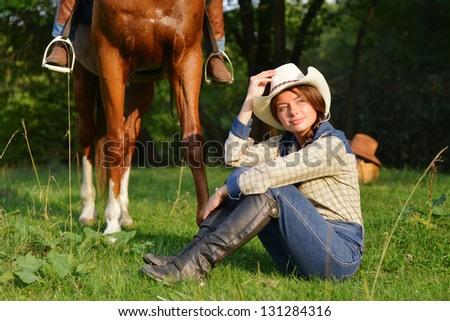Beautiful Smiling Cowgirl with horse - stock photo