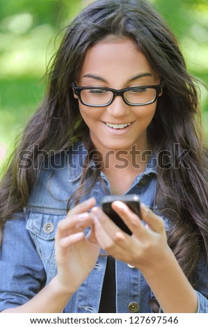 Beautiful smiling dark-haired young woman in denim jacket reads message on phone, against summer green park.