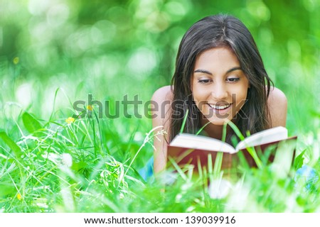 Beautiful smiling dark-haired young woman lying on grass and reading red book, against summer green park.