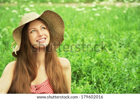 beautiful smiling dreaming woman in a hat lying on the grass in the summer sun and looks aside - stock photo