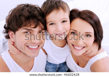 Beautiful smiling faces of  people. A happy young family from three persons - stock photo