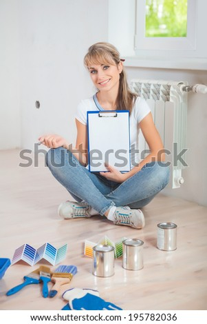 beautiful smiling female painter sitting with crossed legs on floor with other painting tools holding clipboard with blanc sheet of paper and looking at camera - stock photo