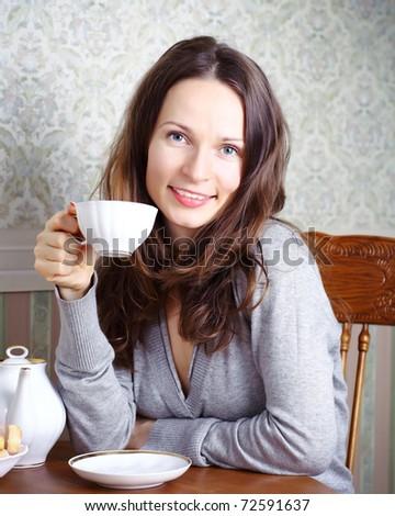 Beautiful smiling girl has breakfast on kitchen - stock photo