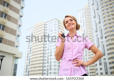 Beautiful smiling girl holds in her hand key to a new apartment on the street