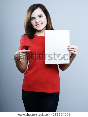 beautiful smiling girl in a red shirt holding a poster with the other hand shows a finger at him - stock photo