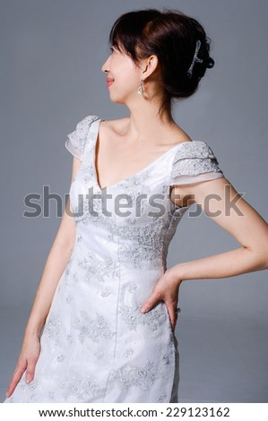 beautiful smiling girl in a wedding dress posing at studio - stock photo