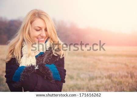 beautiful smiling girl in nature field near forest - stock photo