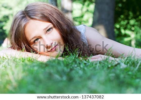 Beautiful smiling girl lying on the grass relaxing
