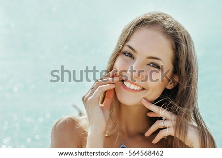 beautiful smiling girl on a blue sky background face close up
