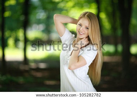 Beautiful smiling girl posing over green summer background - stock photo