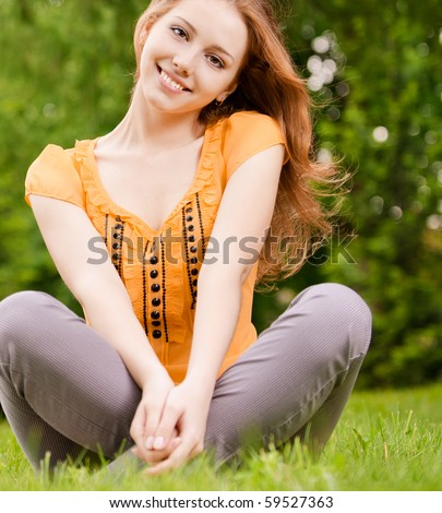 Beautiful smiling girl sits on green lawn in lotus pose. - stock photo