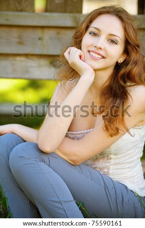 Beautiful smiling girl sits on wooden flooring.