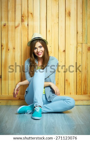 Beautiful smiling girl sitting against wooden background on a floor. Youth teen style portrait.