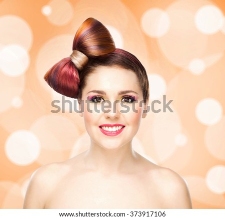 Beautiful smiling girl with a bow haircut and colorful make-up on bubble background. - stock photo