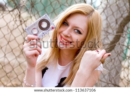 Beautiful smiling girl with a cassette in her hands near the fence - stock photo