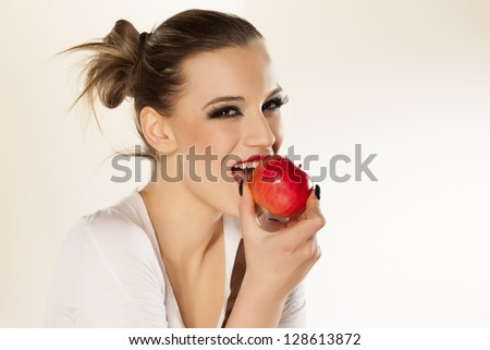 beautiful smiling girl with bright makeup eating red apple on white background