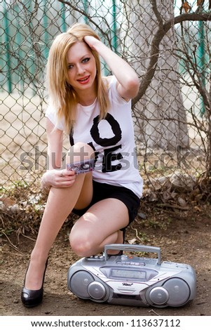Beautiful smiling girl with cassette and tape recorder near the fence - stock photo