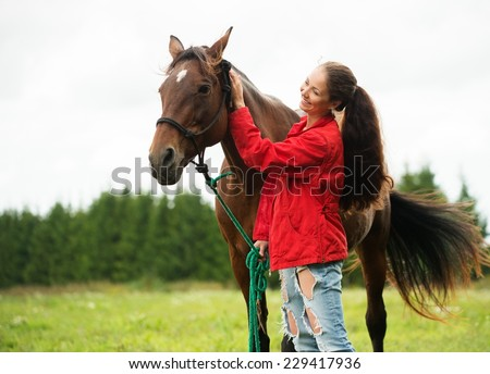 Beautiful smiling girl with her brown horse outdoors  - stock photo