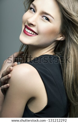 beautiful smiling girl with perfect skin on a dark background - stock photo