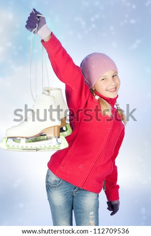 beautiful smiling girl with skates over blue background - stock photo